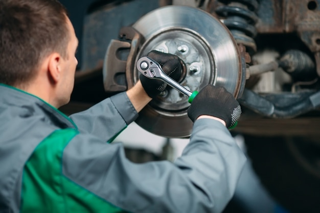 Auto gehesen in autoservice voor reparatie, arbeider repareert het wiel