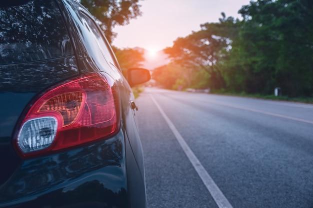 Auto geparkeerd op de weg en klein personenautozitje op de weg gebruikt voor dagelijkse uitstapjes