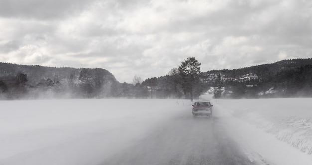 Auto het drijven in de winterblizzard op sneeuwweg in noorwegen