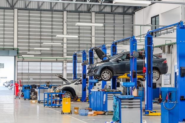 Auto in de hijsapparatuur in de garage die reparatie en moeilijke situatie is