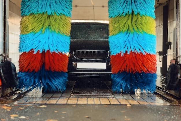 Auto in schuim op automatische wasstraat met kleurrijke borstel