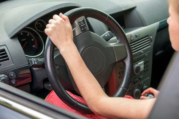 Auto-interieur. dashboard en vrouwenhanden op stuurwiel dat een auto drijft.
