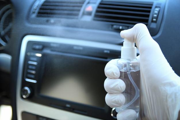 Auto-interieur reinigen en besproeien met desinfectievloeistof. desinfectie van het stuur en de handvatten van de auto. coronavirus bescherming. virusbescherming. desinfecterend voertuig binnenin