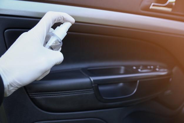 Auto-interieur reinigen en besproeien met desinfectievloeistof. desinfectie van het stuur en de handvatten van de auto. coronavirus, covid-19-bescherming. binnenin desinfecterend voertuig