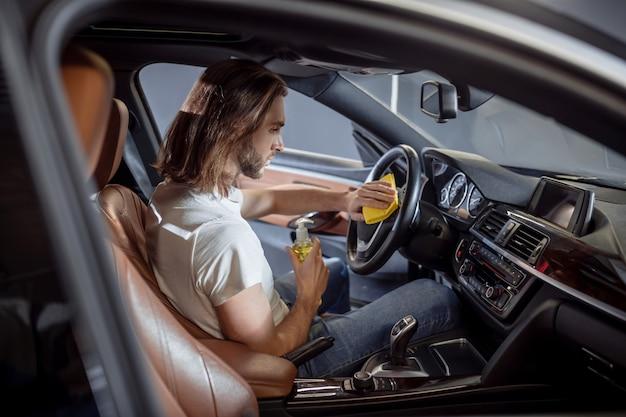 Auto-interieur, schoonmaak. geconcentreerde ernstige jonge langharige man in t-shirt en spijkerbroek afvegen stuurwiel in auto met servet