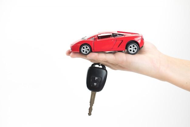 Auto kopen concept. een hand die een autosleutel met een stuk speelgoed auto houdt