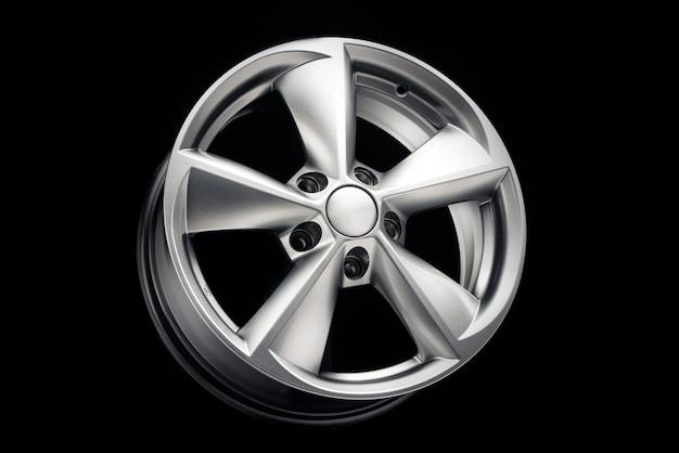 Auto lichtmetalen wiel, nieuwe vijf-spaaks zilver op een zwarte achtergrond, auto-onderdelen voor auto tuning.