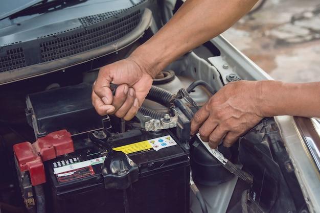 Auto mechanic werken installeer de batterij met sleutel in de garage. reparatie service.