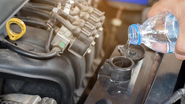 Auto-mechanic werkt het water van het controlesysteem en vult een oude motor van een auto, verandert en herstelt