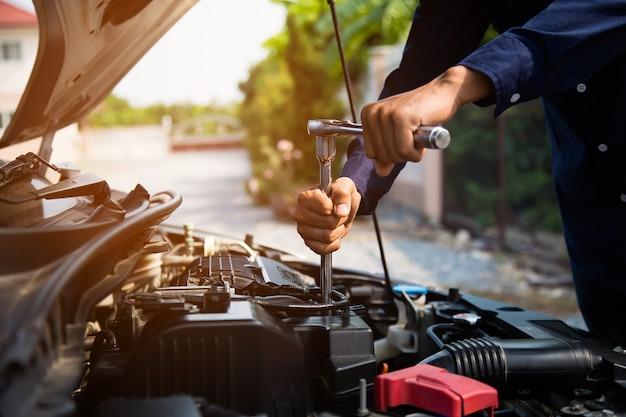 Auto mechanische handen die moersleutel gebruiken om een motor van een auto te herstellen.