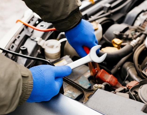 Auto mechanische ingenieur die een moersleutel gebruiken proces om een auto te bevestigen. mannelijke handen van autowerktuigkundige met een moersleutel die in garage werken. mens in handschoenen die in het benzinestation van de autoreparatie werken.
