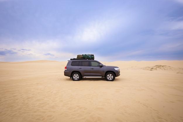 Auto met bagage erop in de woestijn onder een bewolkte hemel overdag