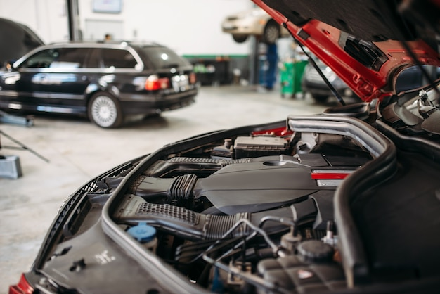 Auto met geopende motorkap in autoservice, motordiagnose.