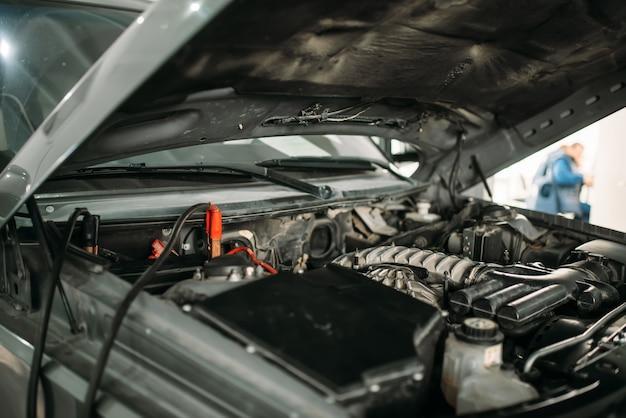 Auto met geopende motorkap, kabel om de accu op te laden