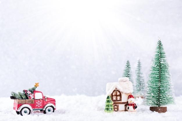 Auto met kerstboom naar landhuis over zilveren achtergrond met sneeuwvlokken