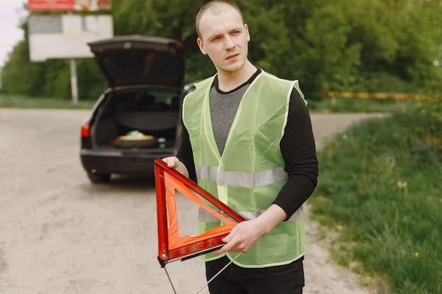Auto met problemen en een rode driehoek om andere weggebruikers te waarschuwen