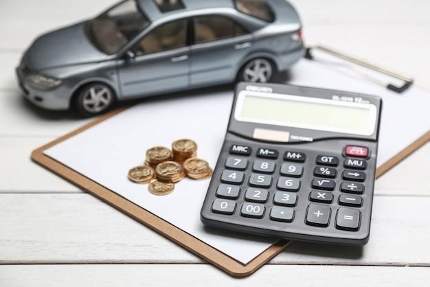 Auto model, rekenmachine en munten op witte tafel