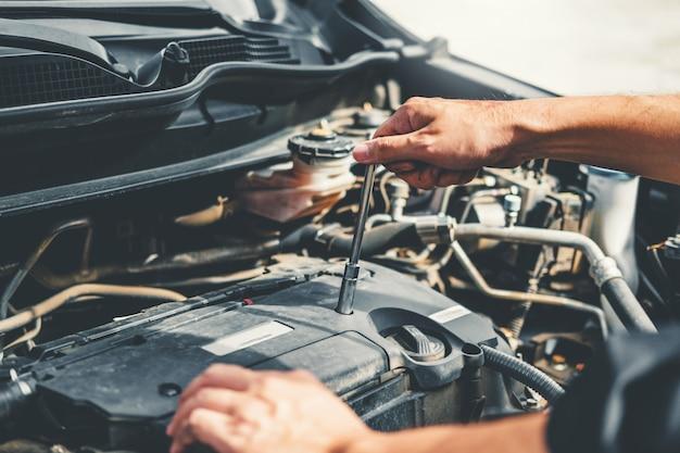 Auto-monteur werken in de garage technicus handen van auto-monteur werken in auto-reparatie