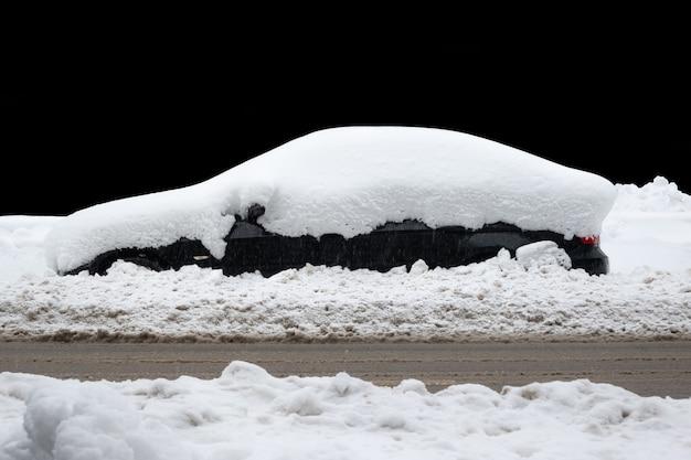 Auto onder dikke deken van sneeuw na storm geïsoleerd op zwarte achtergrond.