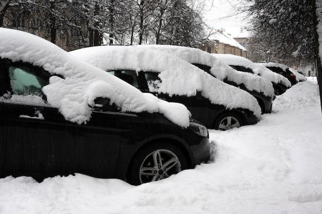 Auto onder dikke deken van sneeuw na storm. voertuigen bedolven onder ijs. niemand