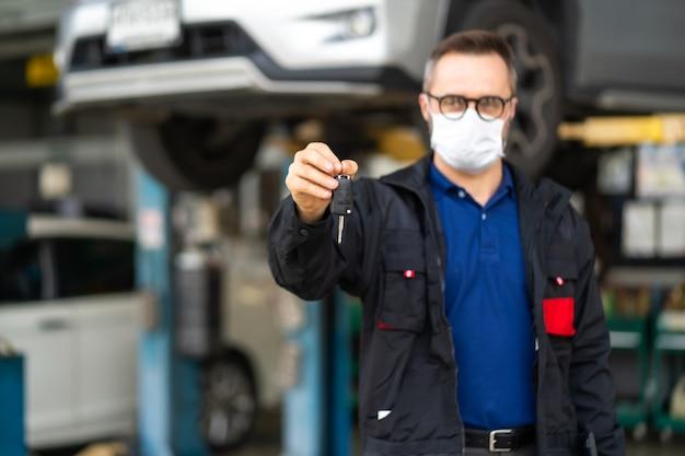 Auto-onderhoud en garage voor autoservice. portret baard mannelijke manager geeft een autosleutel aan camera en draagt medische gezichtsmasker bescherming coronavirus.