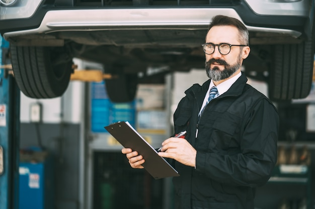 Auto-onderhoud en garage voor autoservice. portret baard mannelijke manager met checklist papier in de hand op auto zorg en auto service garage concept.