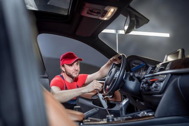 Auto onderhoud. ervaren goed geïnformeerde jongeman in overall die autoservice bedrijf stuurwiel in de cabine