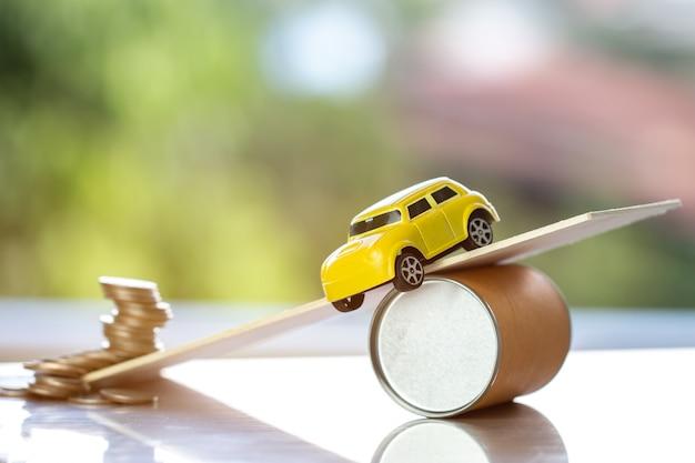Auto-ongeluk en autoverzekering, schuldleningconcept: miniatuurauto op plank valt van de weg / het is als informele schuld of autofinanciering, onveilig reizen in het leven