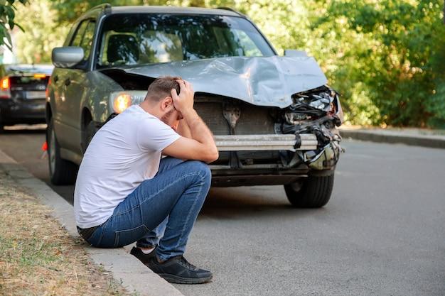Auto ongeluk. man met zijn hoofd na auto-ongeluk. man betreurt schade veroorzaakt tijdens autowrak. man bestuurder is verontwaardigd had een ongeval op de weg. hoofdpijn letsel klap op het hoofd.