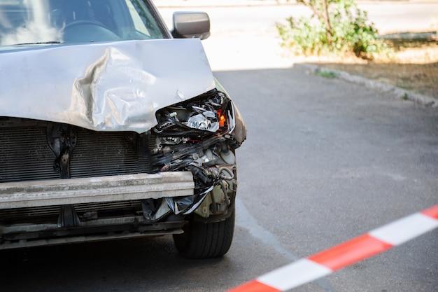 Auto-ongeluk omheind met rode waarschuwingstape. gebroken motorkap van auto op weg. gebroken bumper en autokoplampen met licht op asfalt van het wegdek met kopieerruimte. niemand.