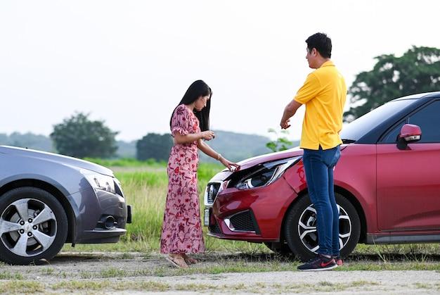 Auto-ongevallenverzekering. mannelijke vrouwelijke chauffeurs na verkeersongeval. mensen na een auto-ongeluk en proberen een vriendelijke overeenkomst te vinden