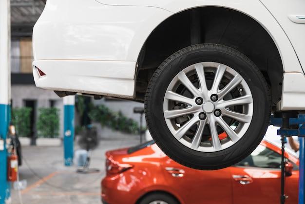 Auto op de lift bij de autodienst die wachten om door monteur te inspecteren. focus op het rechter achterwiel. auto reparatiewerkplaats, automobile professionele service.