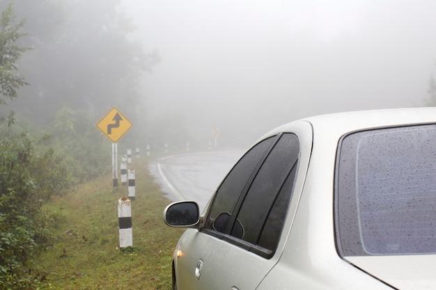Auto op een bochtige weg bij regenachtig en mistig weer