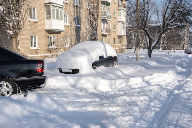 Auto op een straat bedekt met veel sneeuw na een enorme sneeuwstorm