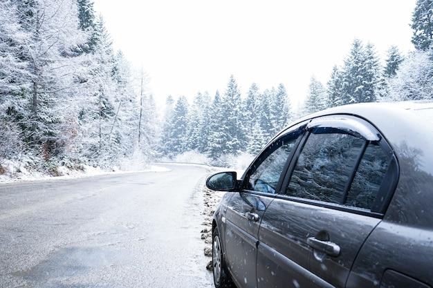 Auto op een winterse weg in het bos