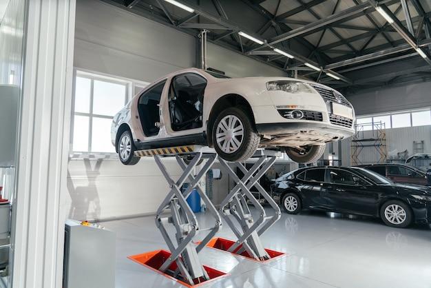 Auto op hydraulische lift bij autoreparatiewerkplaats. auto service concept