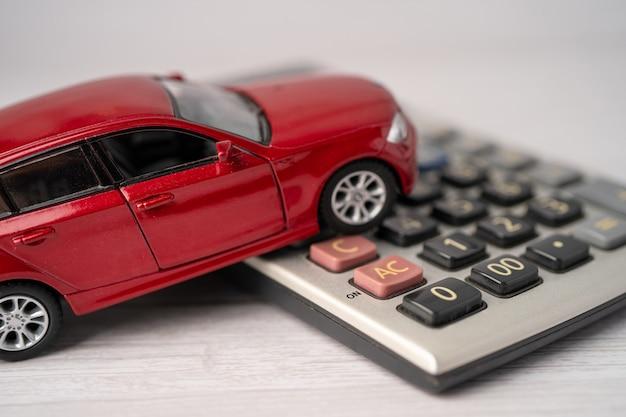 Auto op rekenmachine, autolening, financiën, geld besparen, verzekeringen en leasetijdconcepten.