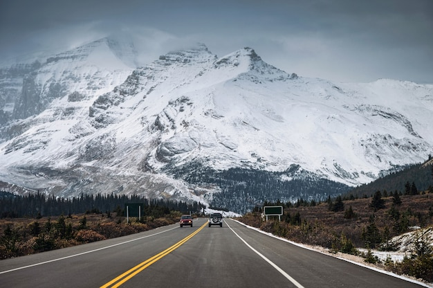 Auto op snelweg en besneeuwde bergketen in somber op icefields parkway, canada