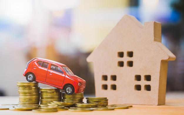Auto op stapel van munten en houten huis