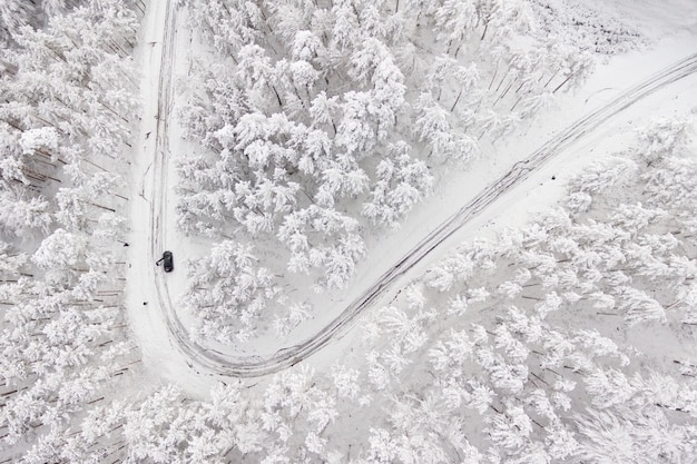 Auto op weg in de winter via een bos bedekt met sneeuw. luchtfoto van een weg in de winter door een bos bedekt met sneeuw. hoge bergpas.