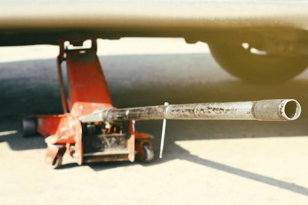 Auto opgetild met rode hydraulische vloer jack selectieve focus.