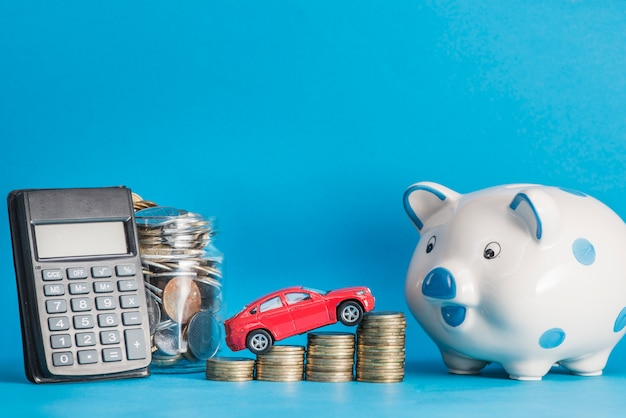 Auto over de muntstapel met rekenmachine; glazen pot; keramiek piggybank tegen blauwe achtergrond