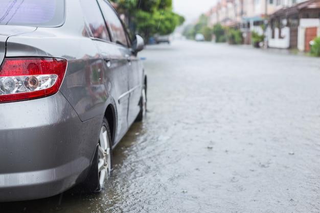 Auto parkeren op straat van dorp terwijl het regent