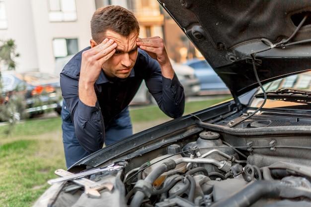 Auto pech concept. de auto start niet. de jongeman probeert alles zelf op te lossen. ze kunnen de auto niet zelf repareren. de verzekering moet alle kosten dekken.