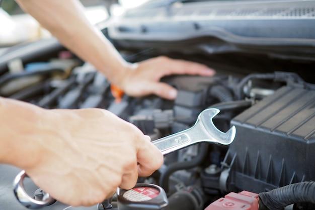 Auto reparateur werkt aan het repareren van de motor.
