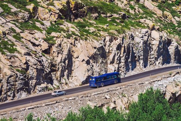 Auto rijdt langs highland highway over afgrond nabij gigantische rotsachtige klif