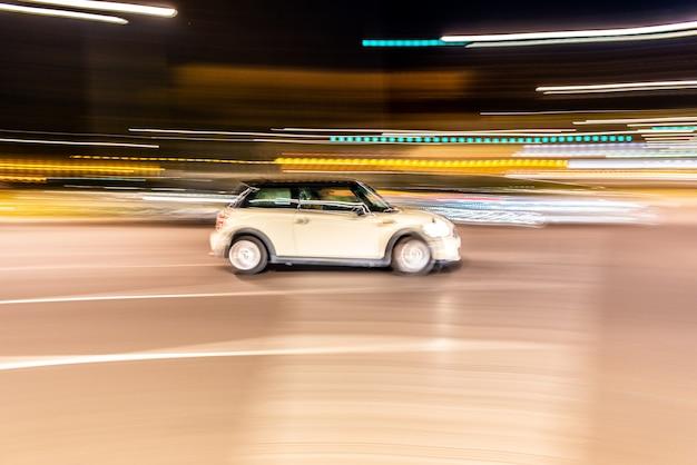 Auto rolt op volle snelheid door de stad 's nachts