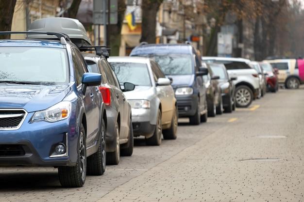 Auto's geparkeerd achter elkaar aan de straatkant van de stad.