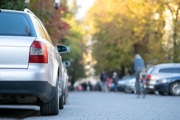 Auto's geparkeerd op een rij aan de straatkant van een stad op een heldere herfstdag met wazige mensen die in het voetgangersgebied lopen.