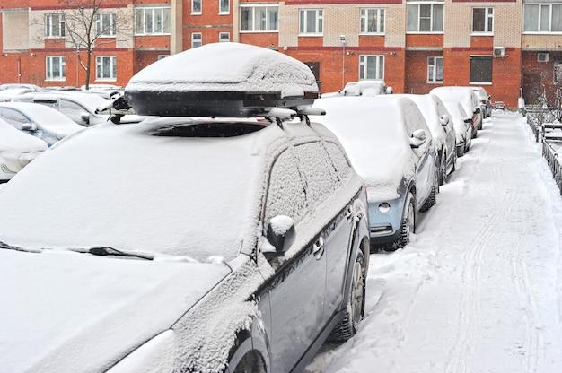 Auto's in de sneeuw worden geparkeerd in de tuin